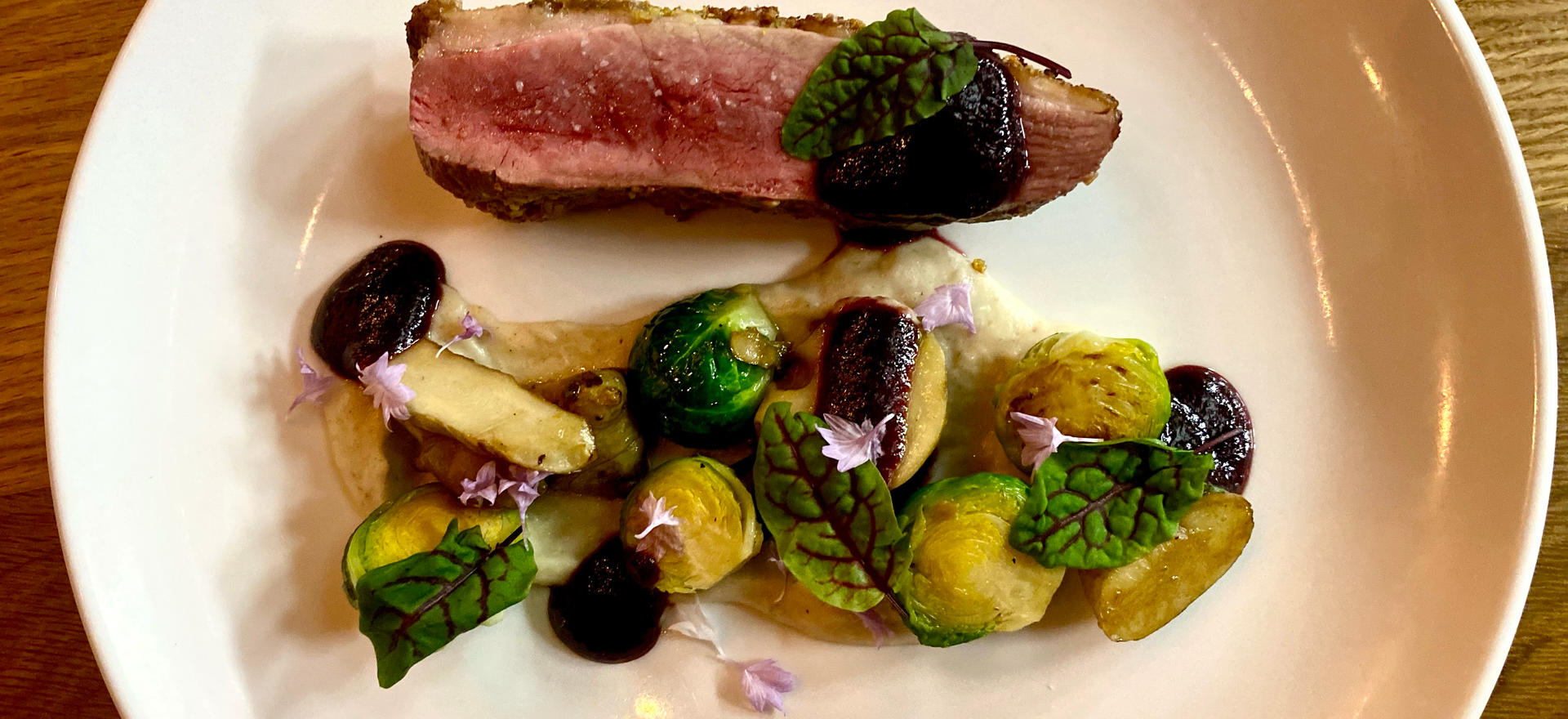 Pistachio Enccrusted Pekin Duck with Sunchokes, Brussel Sprouts, and Cherry Gastrique