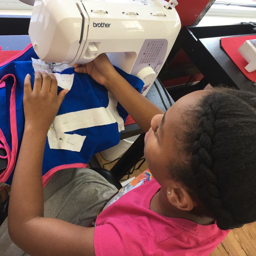 She's almost done! Urielle Greenway, 11, is sewing on her number on the back of her jersey and adding finishing touches.