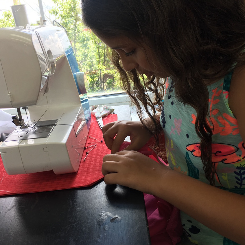 Elizabeth Patel, 10, is sewing the elastic to her jersey.