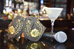 A ornate mariachi bow, a microphone and a cocktail in a martini glass