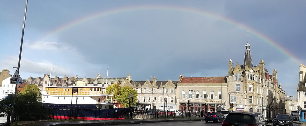 A rainbow over buildings and a boat on The Shore in Leith