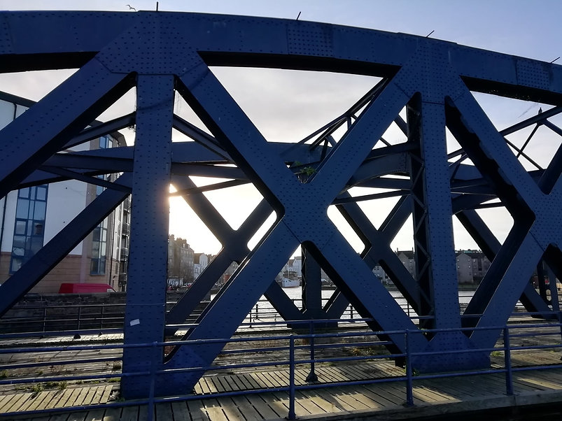 A view through Victoria Swing Bridge in Leith, a blue industrial iron bridge from 19th Century