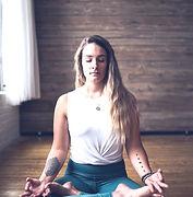woman meditating inside room during dayt