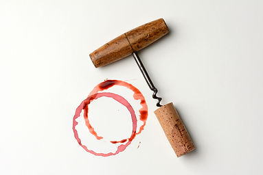 Wine stains cork and corkscrew on paper.