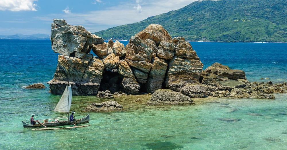 Küçük bir yelkenli tekne kayalık bir oluşum yaklaşıyor