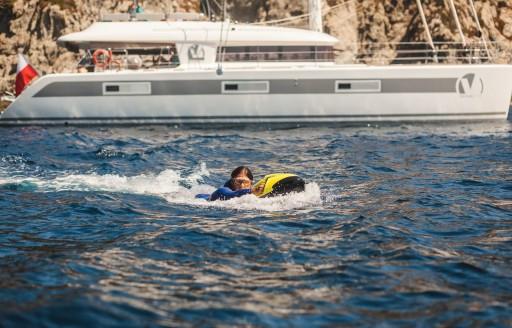 charter konuk Tahiti tatile arka planda lüks katamaran ile SEABOB deniyor