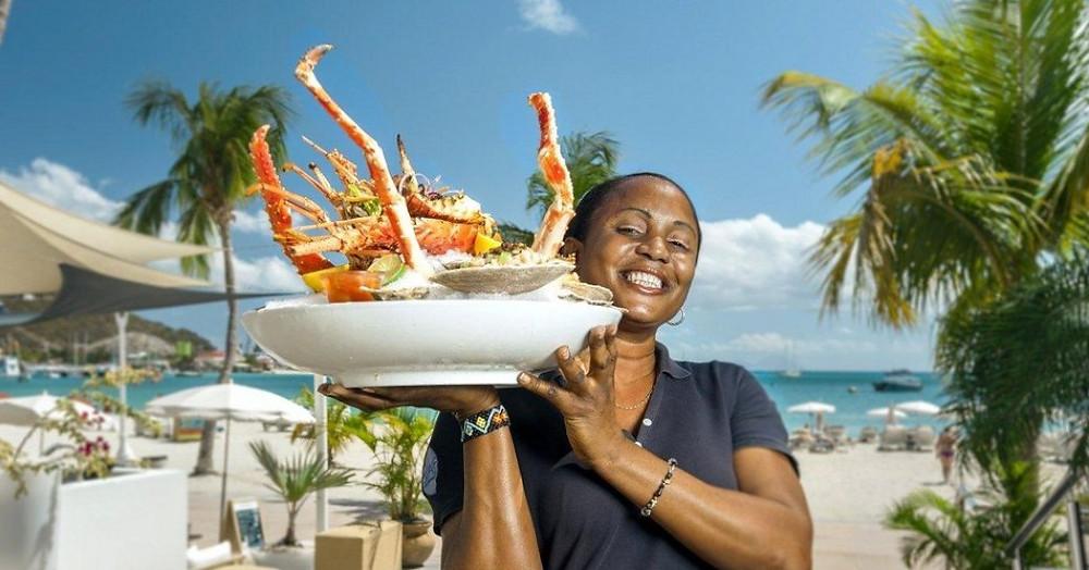 Garson güzel sahil tarafında restoranda büyük tabak Karayip ıstakoz sunmaktadır.