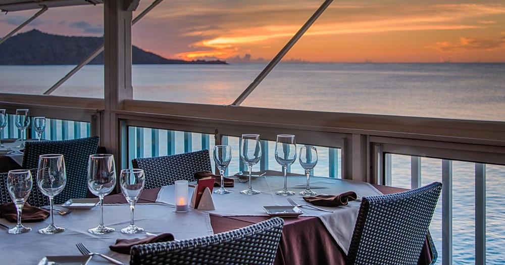 St Martin'de güneşin ufukta batmasıyla sahil kenarındaki masa yemek için ayarlanmıştır
