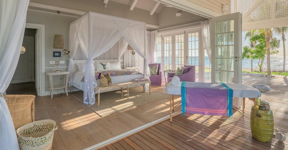 thanda adasındaki villa süiti, terasa açılan kapılar ve masaj masası