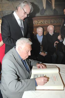"""Will Ferdy ondertekent het """"Gulden Boek"""" van de Stad Antwerpen onder het toeziend oog van Jo Leemans en Jean Walter"""