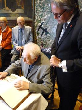 """Will Ferdy ondertekent het """"Gulden Boek"""" van de Stad Antwerpen onder het goedkeurend oog van Schepen Philip Heylen"""