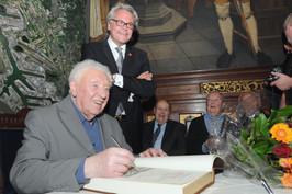 """Will Ferdy ondertekent het """"Gulden Boek"""" van de Stad Antwerpen onder het toziend oog van Walter Van der Smissen en Jo Leemans"""