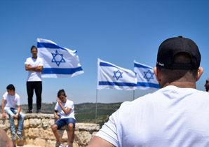 נערים בטיול ודגלי ישראל ברקע