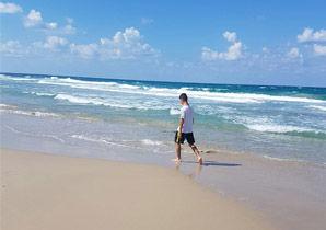 נער צועד על חוף ים