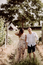 A couple holding hands at a winery on the mornington peninsula. A GLAMPING TIPI setup is seen in the background. Lots of greenery around the couple. The couple are holding hands. She's wearing a flowered dress and he's wearing a white shirt. He's looking into the camera.