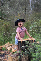toddler girl is looking into the camera while camping. She's wearing a blue sunhat with white dots on it. She's standing before a tree log, and is holding the tree with both hands. She's wearing a vintage pink t-shirt with text on it. She's wearing blue denim girl shorts and is smiling into the camera.