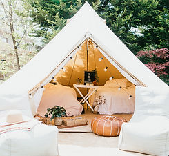 One our unique bell tents, TIPI or Teepee depending on how you name it is all setup for you to experience a private Glamping setup. The TIPI has been placed in front on green trees and includes a grazing box, lounge chairs, queen size bedding and beautiful decoration for our customers to enjoy.