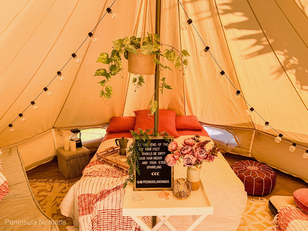 Uniquely styled TIPI Glamping setup on the Mornington Peninsula by Peninsula Nomads. Styled with queen size air mattress, leather ottomans, fairy lights and lounge chairs to create the ultimate experience.