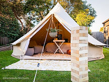 Our canvas bell tipi tent glamping setup on the grass. Completely boho styled and decorated with plants, flowers and lawn games. In front of the TIPI is the Giant Jenga outdoor game.