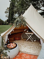 TIPI Glamping Tent for a wedding on the Mornington Peninsula. The teepee is styled with geen flowers and boho themed. Inside is a rug, brown leather ottoman and a white buttler table. The TIPI is setup at a winery and in front of the TIPI is a nice bottle of wine. Next to is can you find a grazing platter with lots of locally sources cheese and meat on it.