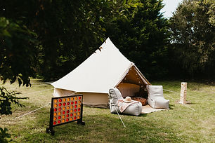 Our bell teepee tent is setup in someone's private garden. In front of the TIPI are 2 ambient lounge chairs and GIant Jenga and Giant 4 in a row placed on the grass.