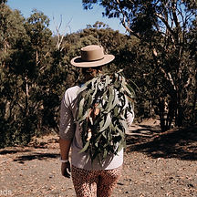 Laura standing with her back facing the camera. Laura is walking in the australian outback and is holding green leaves in her right hand. She's wearing a nude tinted velvet willow & bear hat. She's also wearing a leopard print sports legging and got a white garmin watch on her left wrist. trees and bushes are on both sides of her.