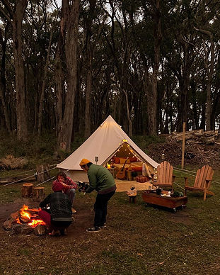 Enjoying a bonfire in front of our TIPI bell tent as part of a Glamping setup on the Mornington Peninsula. Completely styling with outdoor furniture, festival lights and the woods in the background to create your own special adventure.