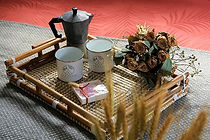 A rattan tray placed on one of the queen size air mattresses peninsula nomads uses during the glamping setip. On top are 2 white camping mugs with the Peninsula Nomads logo on it. Next to it is a coffee machine, a dried flower bouquet and one of our custom branded cookies.