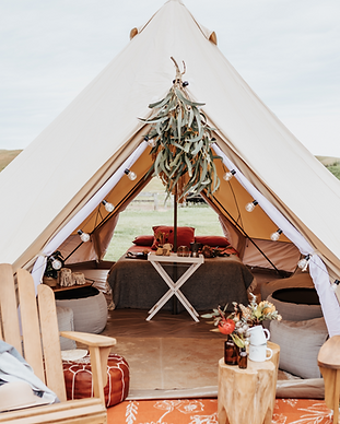 Large Bell TIPI Tent setup at The Ranch in Cape Schank for your unique GLAMPING Experience. The teepee is completely styled and has a unqiue boho feel to it. There is greenery haning outside the tent. Wooden deck chairs are in front of the TIPI to sit on and inside is a Queen Size Air Mattress with bed linen. A white butler table stands in front of the bed to create comfort ans tyle for our guests during their stay on the Mornington Peninsula. A holiday in Victoria truly created for unforgettable moments.
