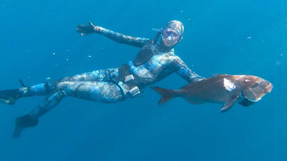 Ange Wallace, Qualitative research based client feedback expert underwater with the snapper she speared.