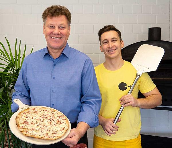 Flammkuchen Profi Andreas Hutter und ein Mitarbeiter präsentieren einen leckeren Flammkuchen