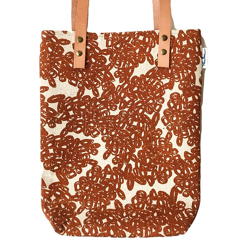 Slim linen tote with leather strap and burnt orange hand screen printed pattern