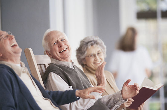 Senior citizens laughing. Elderly people sharing laughter in a care home to reduce stress and anxiety.