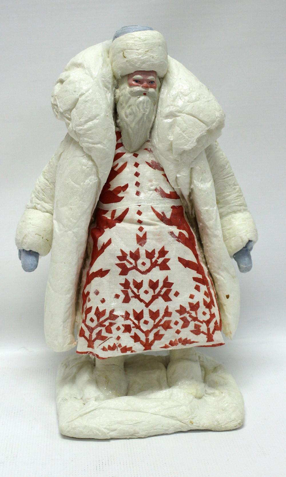 Игрушка «Дед Мороз», 1966 г. Изготовлена  из ваты, бумаги, дерева, металла, выполнена в технике папье-маше  фабричного производства.  Главной отличительной особенностью игрушки является платье с красным геометрическим узором и узким белым поясом при этом белая шапка с голубым донцем.  На руках голубые рукавицы,  на ногах белые валенки. Объёмные, обозначены брови, нос, скулы, прорисованы голубые глаза,  красный рот, розовые щеки - придают сказочность и волшебный вид.  Даритель: Никитин Р.Е.  Место создания: Воронежская фабрика игрушка г.Воронеж