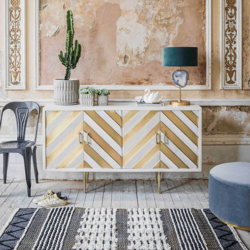 NALA WOOD AND BRASS SIDEBOARD Add show-stopping glamour to a room with our Nala sideboard. Crafted from white mango wood, it features four doors finished with a contrasting chevron pattern in brass. Tapered brass legs further refine this piece, making it an elegant and versatile addition to your home