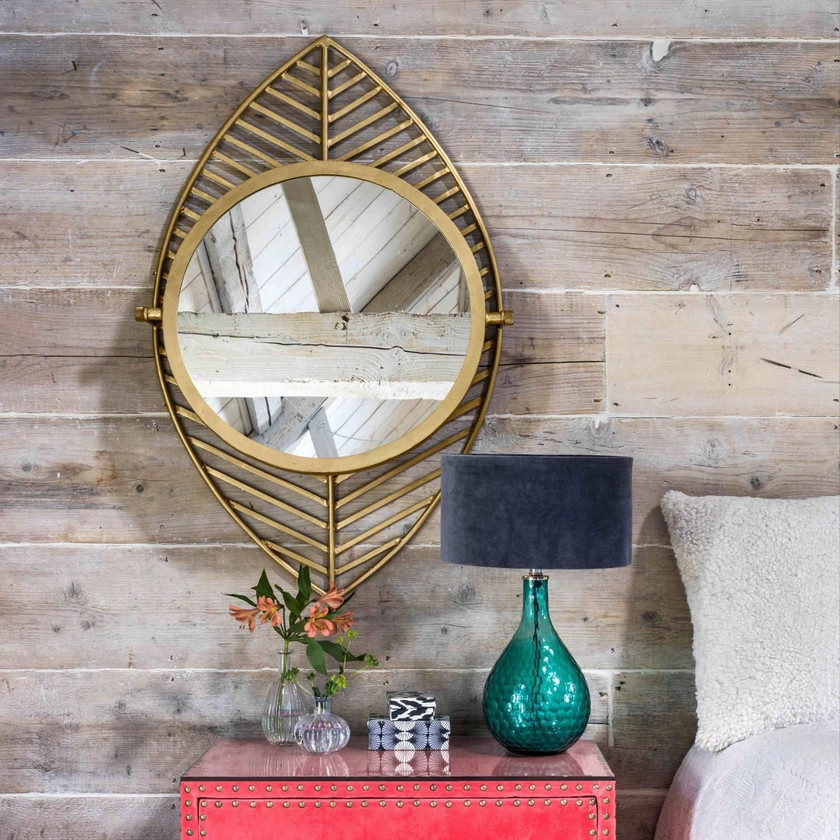 LEAF MIRROR A circular pivoting mirror mounted onto a striking leaf design, crafted from iron with a warm gold finis