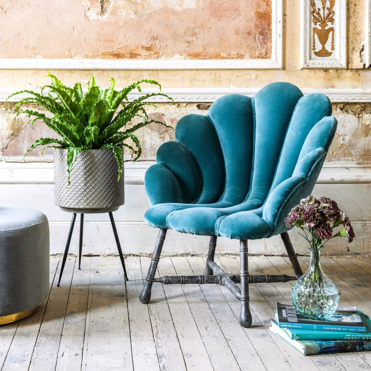 ARIEL TEAL VELVET CHAIR Bring a hint of Art Deco glamour home with our stunning Ariel chair. A sculptural clam-shell design is upholstered in sumptuous teal velvet, with dark carved wooden legs to complete the piece.
