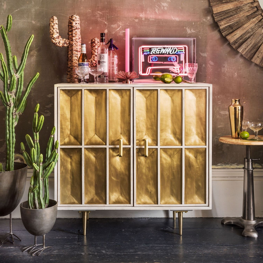 BULLION GOLD SIDEBOARD A striking sideboard handcrafted from mango wood with a whitewash finish and a brass sheet wrap. Featuring a textured front with sleek brass handles, a single shelf and mid-century style tapered legs.