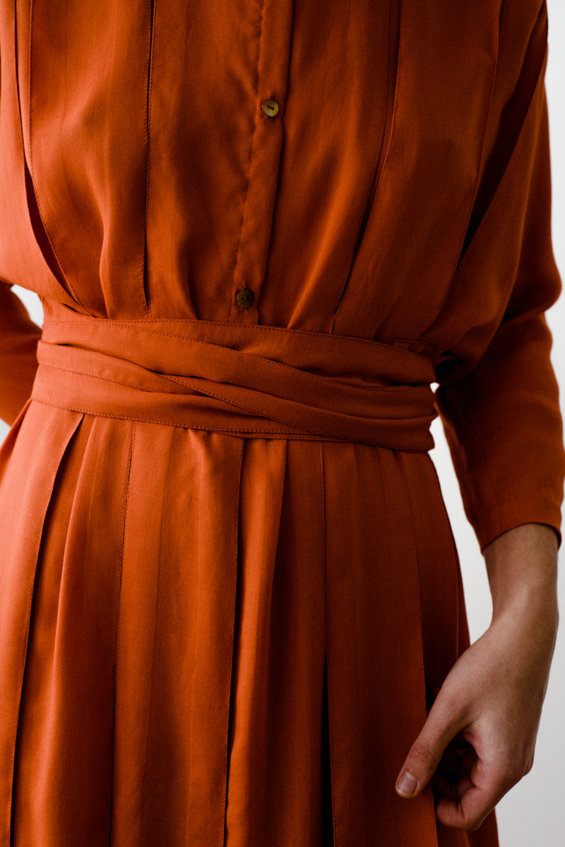LIBOS  Libos is a knee-length dress with three-quarter sleeves, inverted pleats, round neck, front closure and has a ribbon on each side.   Made of fine woven wool.   out of stock
