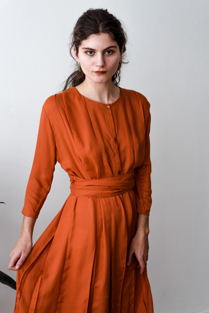 LIBOS   Libos is a knee-length dress with three-quarter sleeves, inverted pleats, a round neck, a front closure and has a ribbon on each side.   Made of fine woven wool.   out of stock