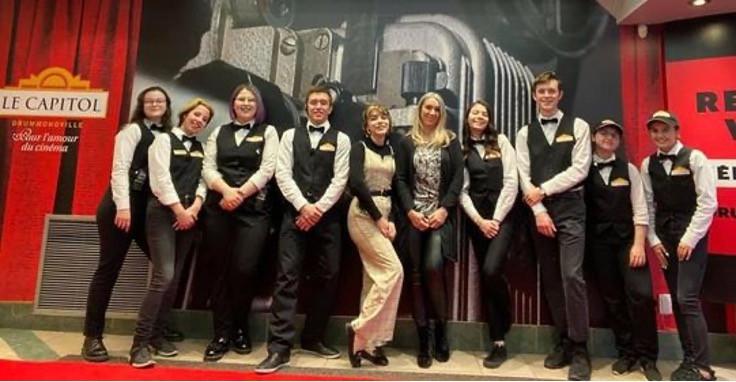 Les employés du Capitol revêtant leur uniforme de croupier en compagnie de la directrice du cinéma Annie Hamel (sixième à partir de la gauche).