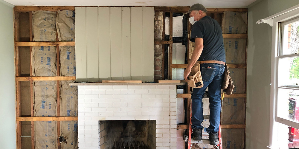 断熱材を壁に挿入している大工さん。