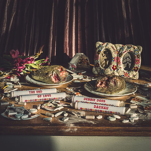 Erotic Secrets of Pompeii's single The End of Love. Released 27th November 2020. Macabre vanitas artwork by Dave Sausins (ElderflowerYouth). surreal still life, salvador dali. glitter hearts, loverhearts, smahsed crockery, pills, Debbie does Dachau.