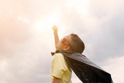 Boy with cape looking upward