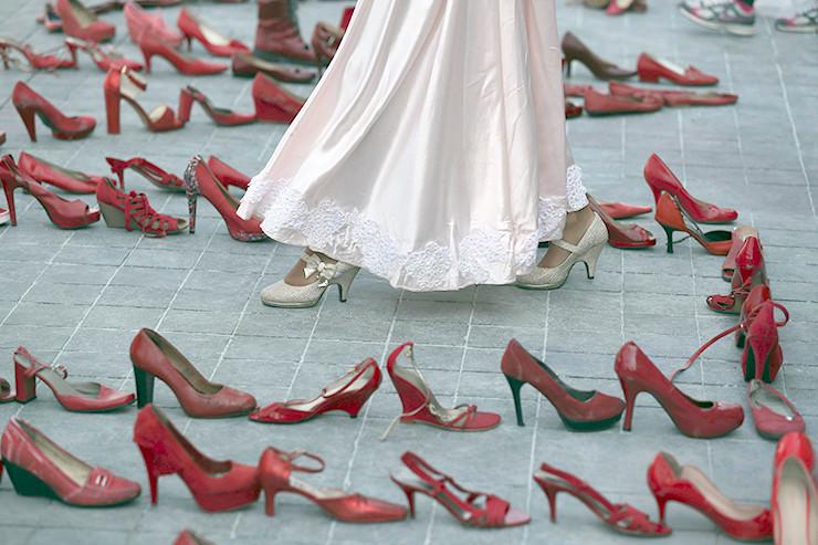 """Eine Schauspielerin geht durch rote Schuhe, die am """"Tag ohne Frauen"""" ermordete Frauen darstellen sollen."""