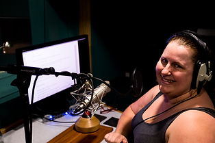 A woman looking at camera smiling wearing headphones in front of a microphone, desk and computer monitor in a recording studio.