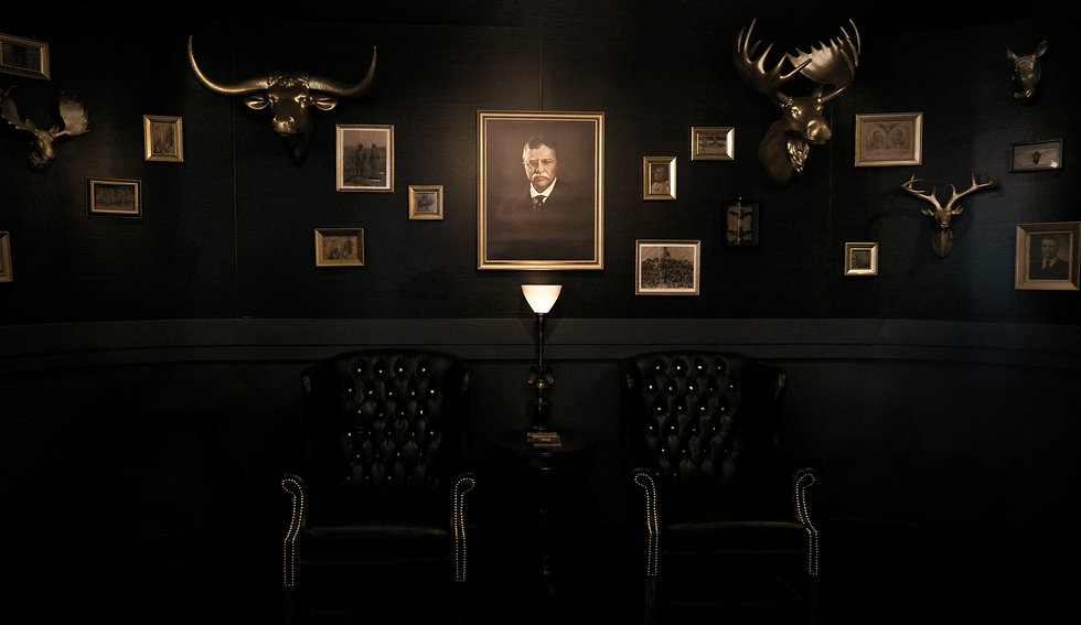 Portrait of Teddy Roosevelt, smaller frames and mounted bull and moose heads, above 2 wingback chair