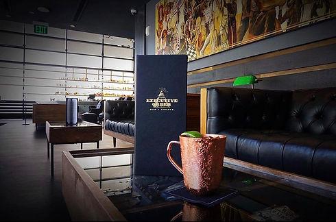 Menu on a coffee table next to a copper mug