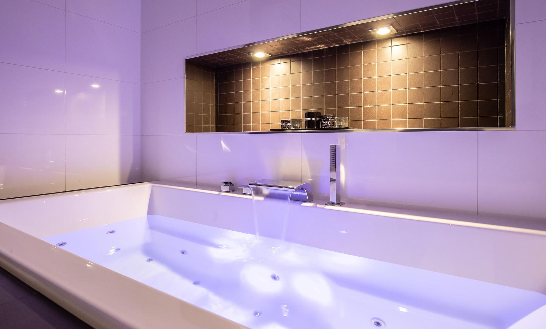 Een badkamer met verlichting waar je uren in kunt doorbrengen omdat het lichtplan van De Lichtplanners klopt.