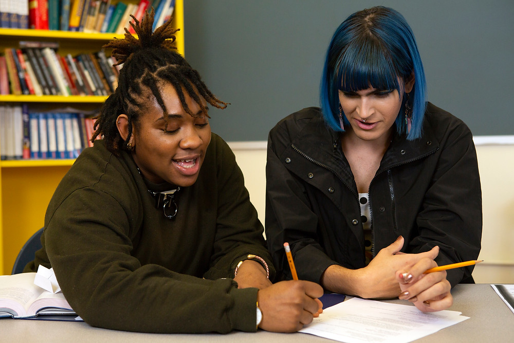 Two Non-binary students doing classwork together.